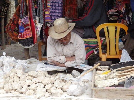 Petite pause lecture en attendant le client au marché de Chichicastenango au Guatemala photo blog voyage tour du monde travel https://yoytourdumonde.fr