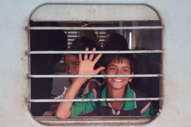 Wagon avec un enfant entrain de sourir dans la gare de jaipur photo blog voyage tour du monde https://yoytourdumonde.fr