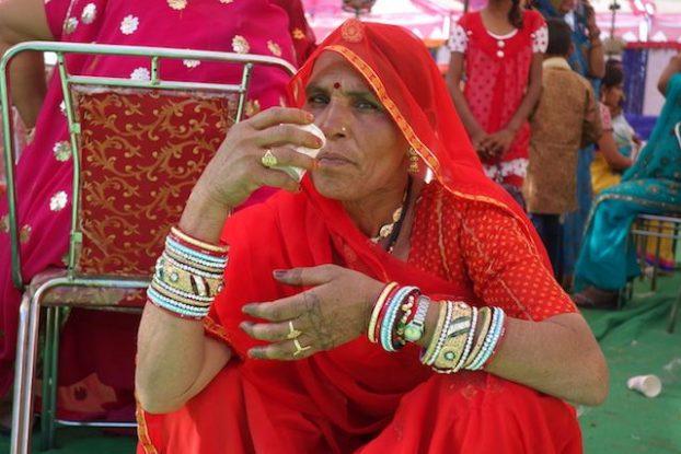 Une femme indienne lors d'un mariage en inde à pushkar qui attend la ceremonie avec du thé photo blog voyage https://yoytourdumonde.fr