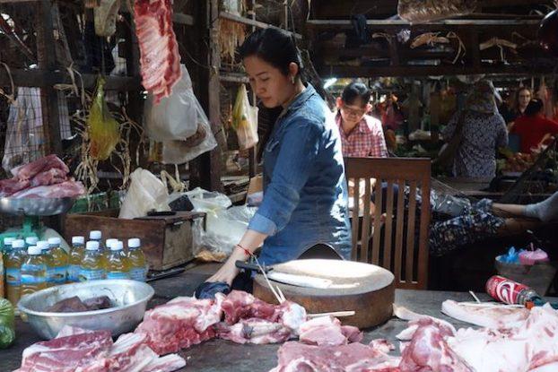 Devant un stand de viande sur le marché de Kampot au Cambodge. Photo yoy tour du monde https://yoytourdumonde.fr