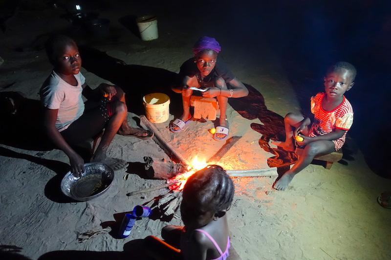 Des enfants racontent leurs journées devant un feu, culture diola, casamance, sénégal, photo blog voyage tour du monde https://yoytourdumonde.fr