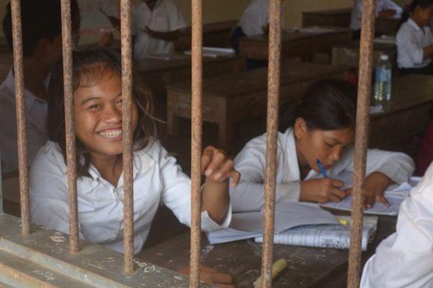 Une ecoliere qui sourie derrière les barreaux de son ecole au cambodge à Kep. Photo https://yoytourdumonde.fr