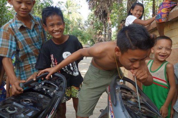 aide d'un jeune birman en lui donnant de l'essance pour qu'il reparte photo blog voyage https://yoytourdumonde.fr