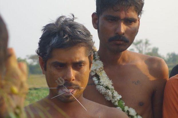 ceremonie hindouiste avec un fidele qui s'automitile la langue avec les insignes de shiva photo blog tour du monde https://yoytourdumonde.fr
