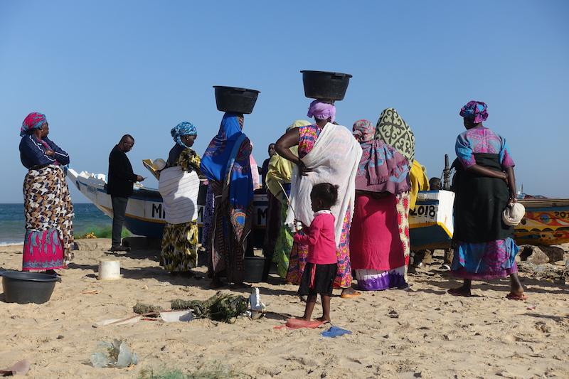 Les femmes attendent les bateaux remplis de poissons et les pêcheurs du coté de Popenguine au Sénégal photo blog voyage tour du monde https://yoytourdumonde.fr