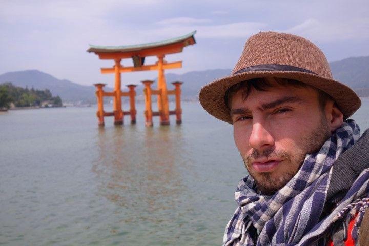 Portrait de Yohann Taillandier devant le celebre Tori de Miyajima photo blog voyage tour du monde https://yoytourdumonde.fr