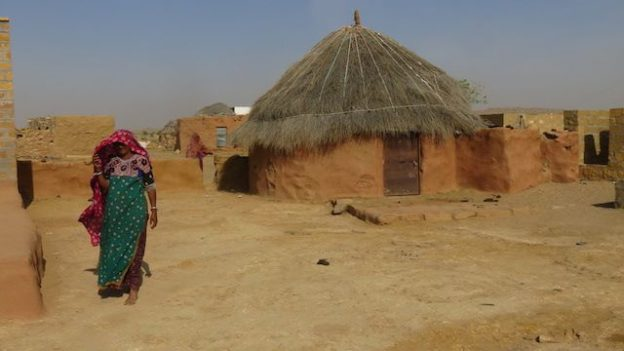 Une femme marche dans son village dans le desert de Thar photo voyage tour du monde https://yoytourdumonde.fr