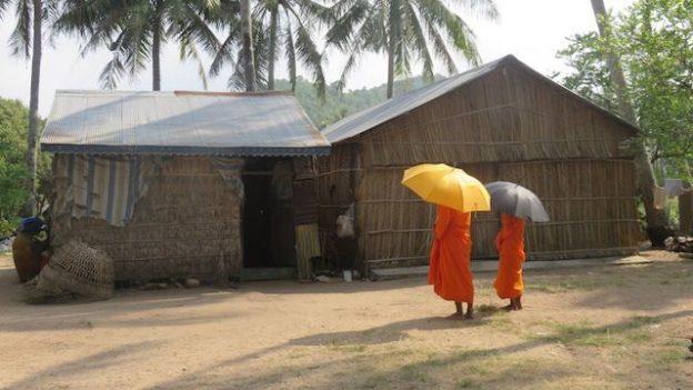 Des moines bouddhistes qui font l'aumone pres d'une maison dans un village du cambodge