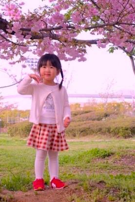 Une petite fille japonaise devant un cerisier en fleur à Osaka photo blog voyage tour du monde https://yoytourdumonde.fr