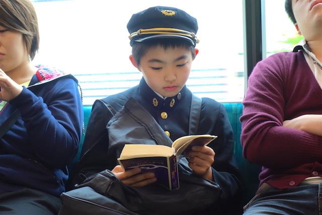 Enfant japonais habillé en tenue scolaire dans le métro de Tokyo.