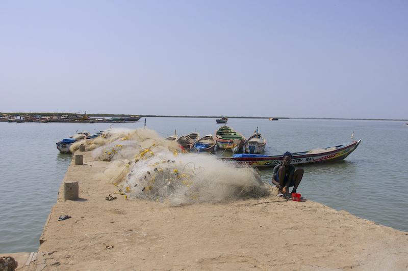 Un pêcheur sur le ponton du port de Ziguinchor en Casamance au Sénégal photo blog voyage tour du monde https://yoytourdumonde.fr